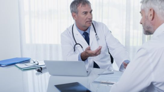 Two clinicians using a computer during a consultation.