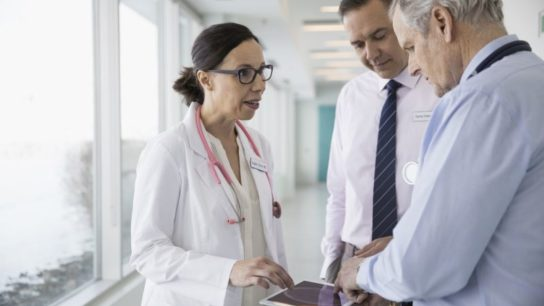 Clinicians consulting over a tablet