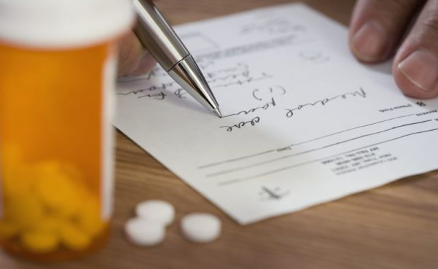 A doctor writing out a prescription.