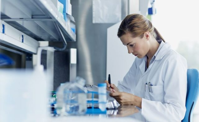 Doctor writing down results in a lab.