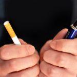A man holding an e-cigarette and a cigarette