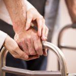 Clinician helping an elderly patient use a walker