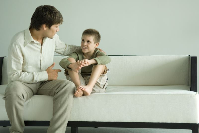A father and son sitting together on a sofa