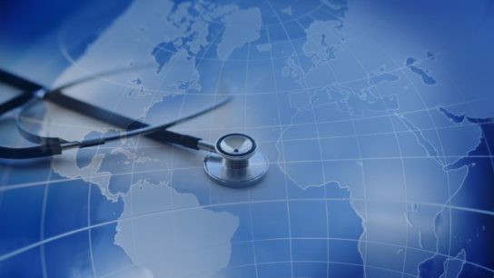 A close-up of a stethoscope on an international map