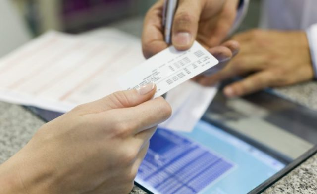 A patient hands over her health insurance card at a clinic.