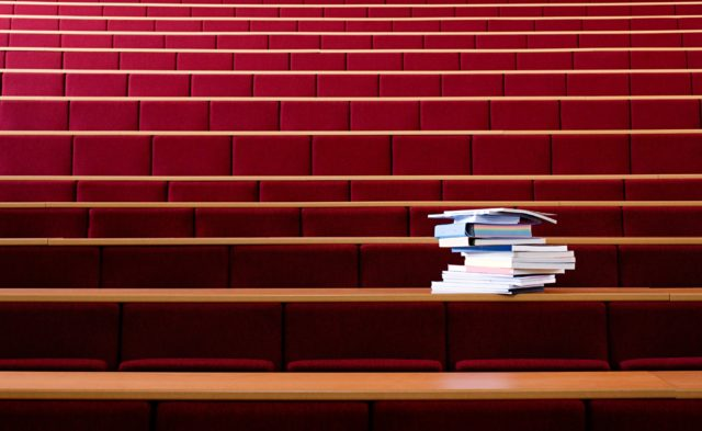 an empty lecture hall with a stack of books on the table
