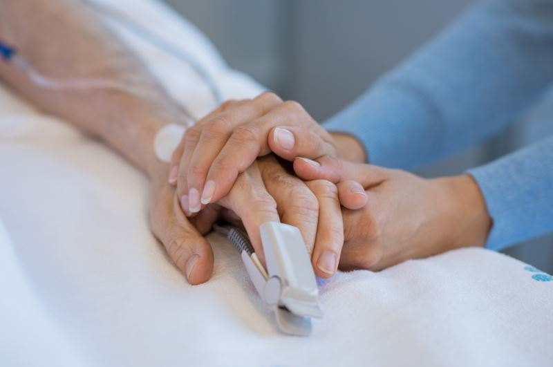 Daughter holding the hand of an elderly father.