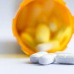 A prescription bottle of pills spilled over