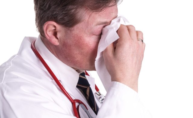 Physician working while sick with influenza.