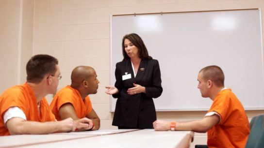 A woman talking to inmates