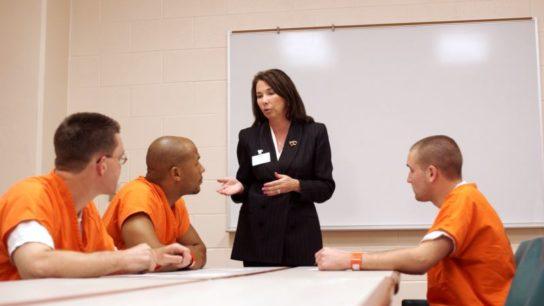 A woman talking to inmates