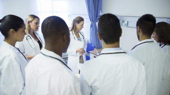 Medical students examining a patient