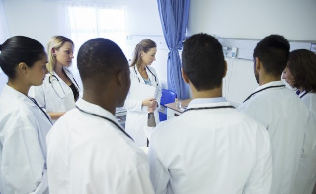 Medical students examining a patient
