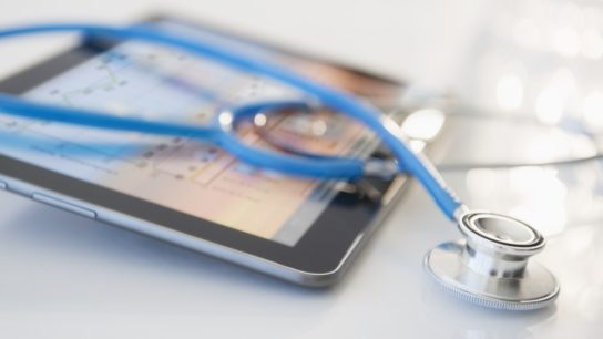 Stethoscope lying on a tablet displaying medical data
