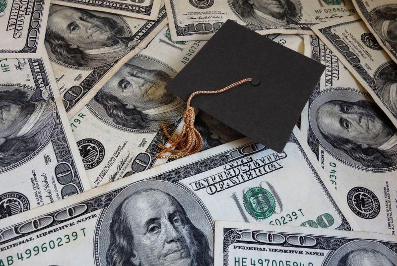 A graduation cap on a pile of money