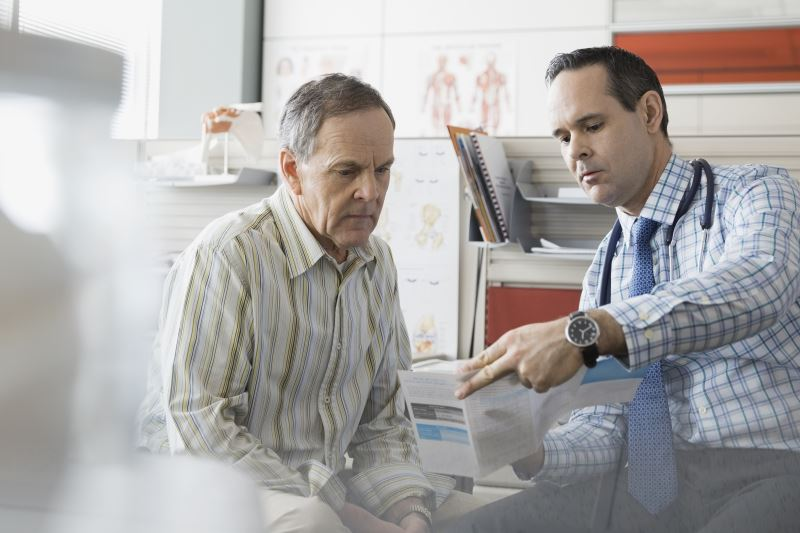 A doctor showing a patient a brochure