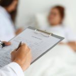 Physician, patient, examine, hospital bed, clipboard, patient chart