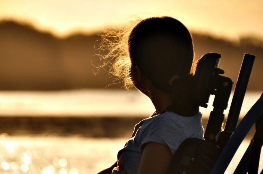 Girl with cerebral palsy sitting in wheelchair at sunset