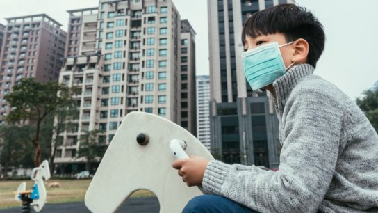 Child wearing a mask in a polluted city.