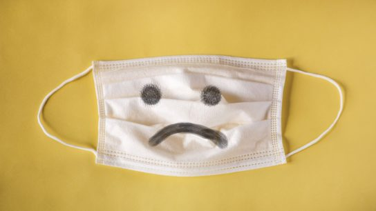 A flu mask against a yellow background.
