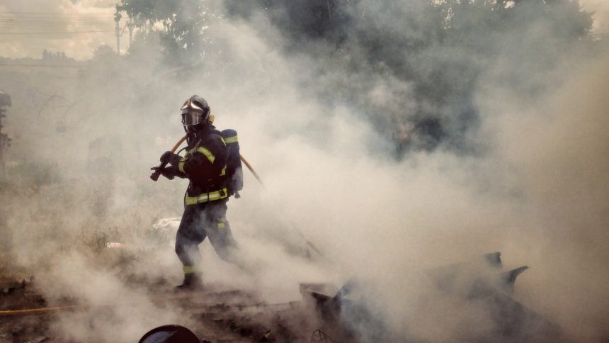 A firefighter in a very smoky area.