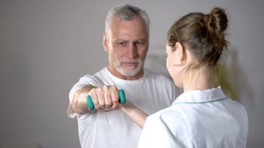 A nurse helps a patient perform a dumbell exercise.