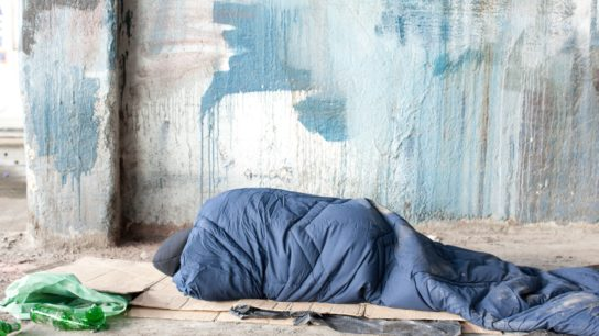 A homeless person sleeps on the sidewalk in a sleeping bag.