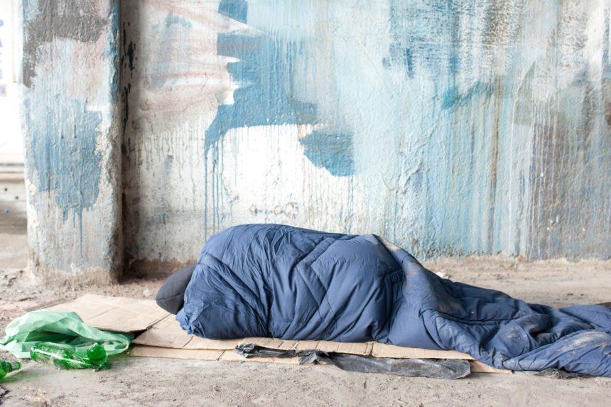 A homeless person sleeps on the sidewalk in a sleeping bag.