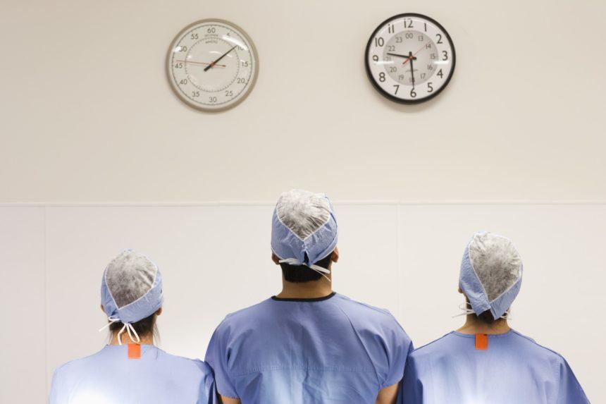Doctors in scrubs look at clocks.
