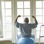 An older patient does physical therapy in his home.