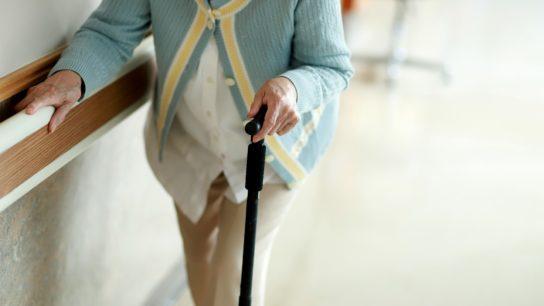 An older woman walks in a hospital hallway.