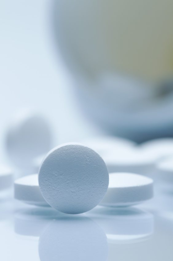 A bottle of white pills spilling onto a table.