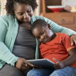 child and mom on tablet