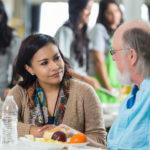 Woman talking to senior man in food bank soup kitchen