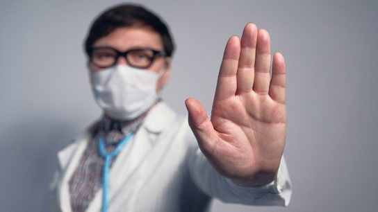 Doctor holding up hand to signal stop