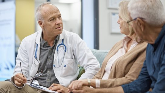 Doctor apologizing to couple in the waiting room