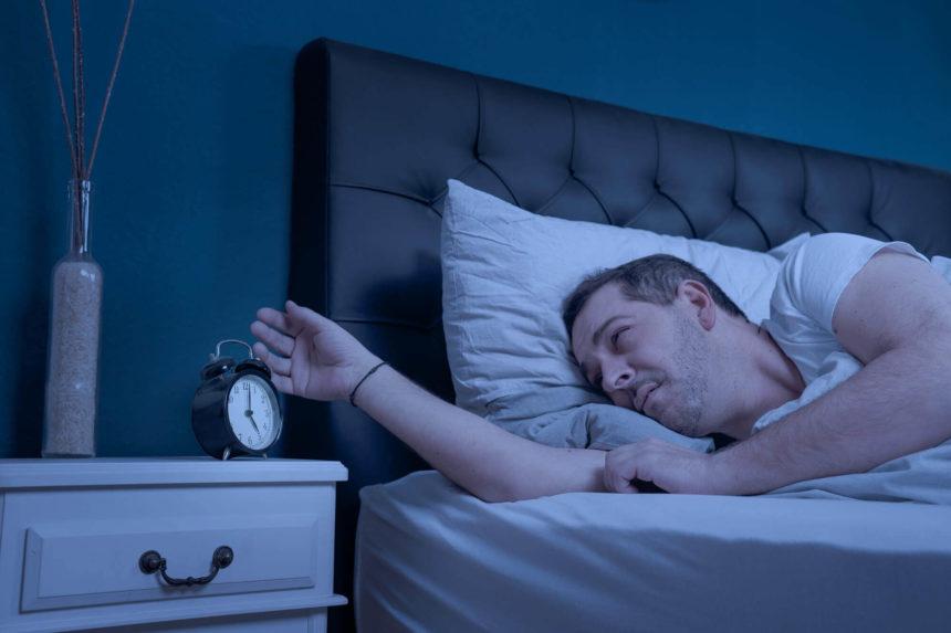 man who cannot sleep looking at alarm clock